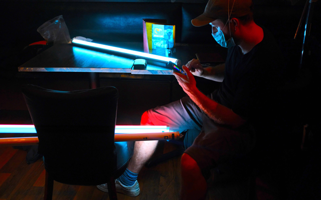 Cinematographer Alfie Thirole setting up wireless light tubes for outdoor police lights.